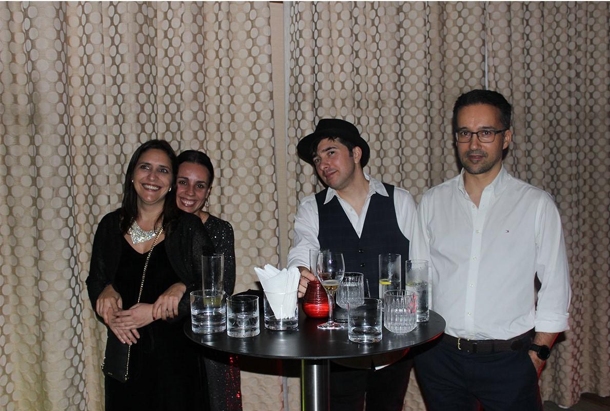 Duas mulheres de roupa escura e dois homens de roupa branca copos